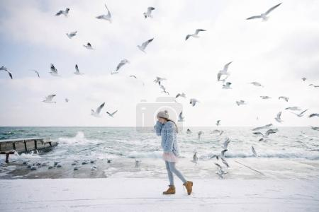 Photo for Stylish young girl on winter seashore with seagulls - Royalty Free Image