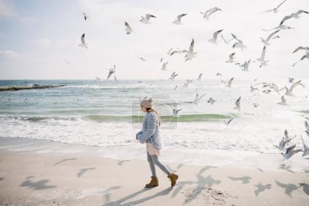 Photo for Beautiful stylish girl on winter seashore with seagulls - Royalty Free Image