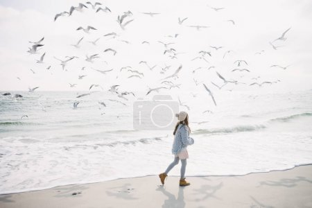 stylish girl running on winter seashore with seagulls