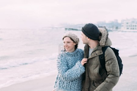 smiling couple hugging and walking on winter seashore