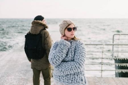 stylish girl in merino sweater on winter quay, boyfriend standing behind and looking at sea