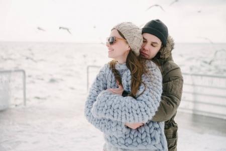 Photo pour Jeune copain étreignant sa copine élégante sur le quai d'hiver - image libre de droit