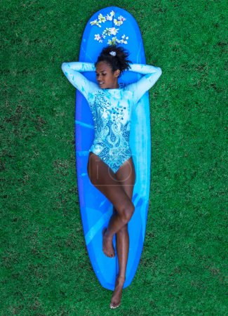 Surfer girl with afro hairstyle in blue one piece bikini lying on the back on blue longboard on green grass