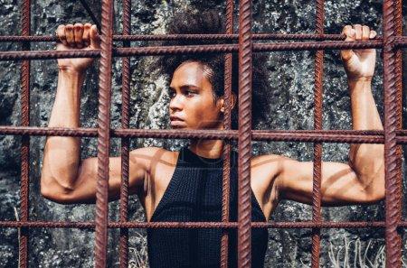 """Photo pour Tout le pouvoir au peuple. Hommage à Black Panther Party et Angela Davis, s'inspire de sa célèbre image au pochoir """"Libérez Angela et tous les prisonniers politiques"""" des années 60. Belle fille athlète ajustement avec afro derrière barres de fer rouillées . - image libre de droit"""