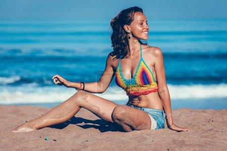 Beautiful girl enjoying sun bath on the beach in blue water