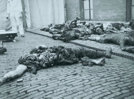 Corps of heavily burned men laying down sidewalk and street