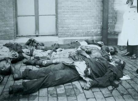 Dead civilians laying down sidewalk in town