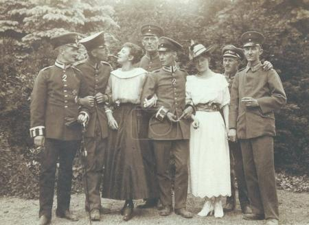 German soldiers with two girls posing in park at camera