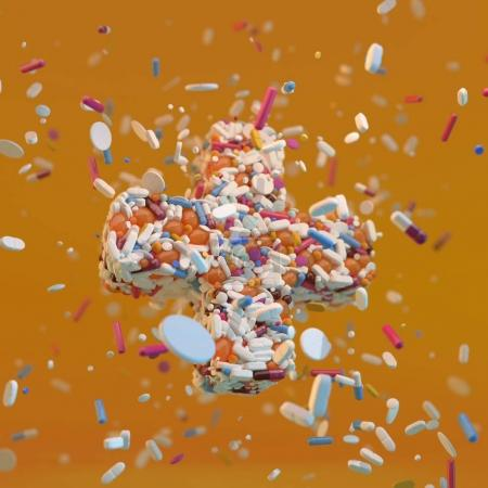 3d rendered pharmacy cross fulfilled with different type of pills on yellow background