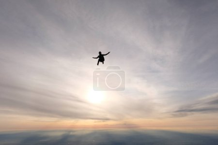 Skydiving. A skydiver is flying in the sky.