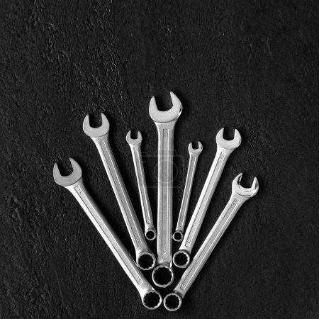 Photo for Bunch of wrenches on black textured background. - Royalty Free Image