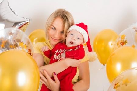 Newborn baby with mom on the background of Christmas balls