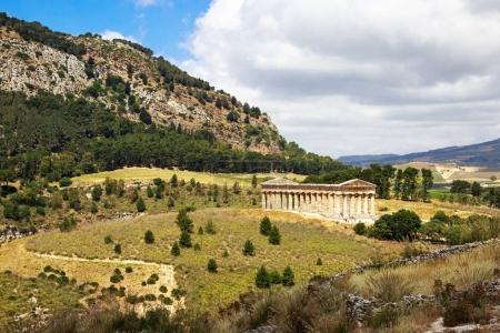 Ancient ruins of stone temple and green nature, view from hilltop town of Segesta in Sicily, Italy.