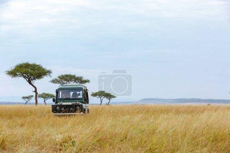 Safari vehicle driving through an open grass field in Kenya, Africa