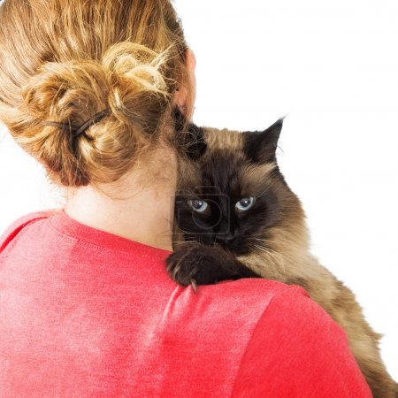 Cat looking over the shoulder of a woman that is carrying it in her arms
