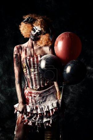 Photo pour Mauvais clown roux taché de sang tenant des ballons. Clown zombie femelle. Halloween. Horreur . - image libre de droit