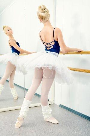 Photo pour Belle danseuse de formation près de la barre de ballet dans une classe de ballet. - image libre de droit