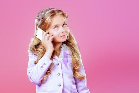 Photo pour Jolie petite fille avec des cheveux blonds beau parler sur son téléphone portable sur fond rose. Petite princesse avec une couronne sur sa tête. Kids fashion. - image libre de droit