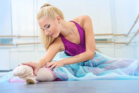 Photo pour Belle danseuse faisant s'étend dans une classe de ballet. - image libre de droit