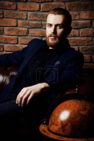 Photo for Imposing well dressed man sitting on a Chesterfield leather couch. Men's beauty, fashion. - Royalty Free Image