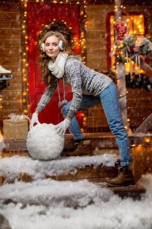 Photo pour Jolie fille dans des vêtements d'hiver fait une grosse boule de neige pour un bonhomme de neige près de sa maison décorée pour Noël. Merry Christmas and Happy New Year. - image libre de droit