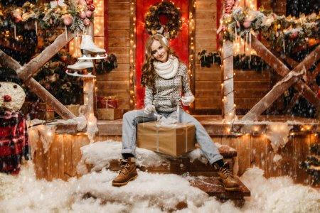Photo pour Jolie fille dans des vêtements d'hiver est assis sur le porche d'une maison décorée pour Noël et tenant une boîte-cadeau. Temps des miracles. - image libre de droit