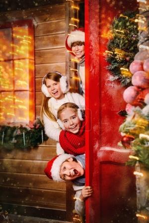 Photo pour Groupe d'enfants lit dehors par derrière la porte de la maison décorée pour Noël. Merry Christmas and Happy New Year. - image libre de droit