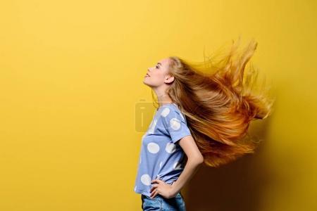 Photo pour Jolie fille avec de beaux longs cheveux volants sur fond jaune. Cheveux sains, soins capillaires . - image libre de droit