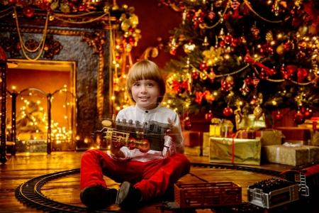Photo for Cute five-year-old boy playing with a toy railway near the Christmas tree. Christmas night. Christmas decoration. - Royalty Free Image