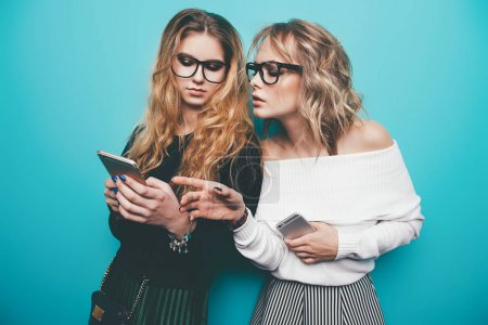Photo for Two pretty girls using their smartphones and  posing in studio over blue background. Modern lifestyle. Studio shot. - Royalty Free Image
