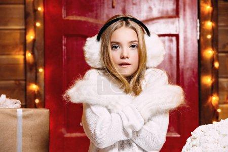 Photo pour Fille jolie enfant est debout près de sa maison décorée pour Noël en mitaines et cache-oreilles fourrure. Accessoires d'hiver chaud. Merry Christmas and Happy New Year. - image libre de droit