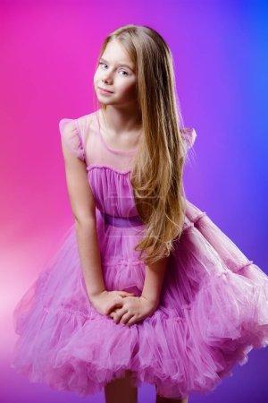 Photo pour Portrait d'une jolie fille de neuf ans dans une robe élégante sur fond rose. Beauté et santé des enfants . - image libre de droit