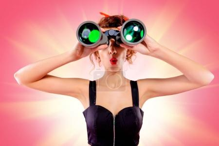 Photo for Pretty red-haired girl looks through binoculars at something over pink background. Pin-up style. - Royalty Free Image