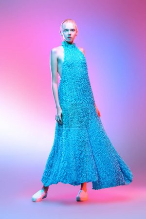 Photo for Vogue shot of a female model posing at studio girl in a long knitted dress. Fashion collection. Full length portrait over pink background. - Royalty Free Image