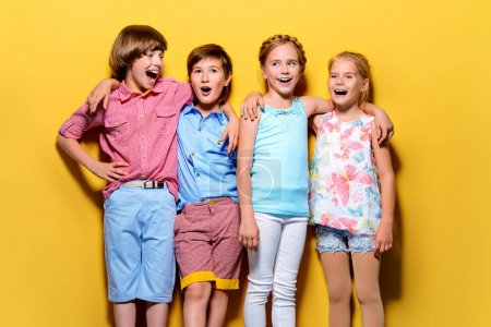 Photo for Bright summer children. Group of joyful children posing together over bright yellow background. - Royalty Free Image
