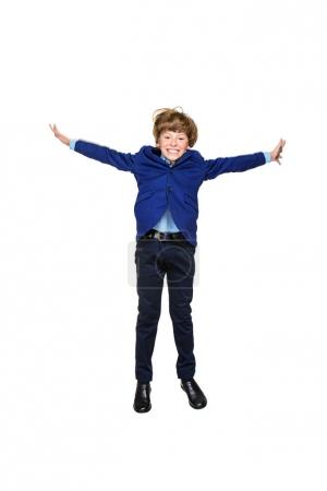 Photo for Happy excited boy in school uniform jumping for joy. Isolated over white background. School fashion. Copy space. - Royalty Free Image