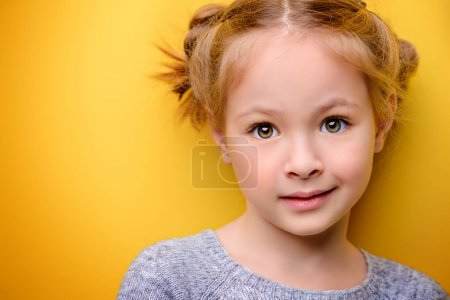 Photo for Close-up portrait of a cute little girl. Studio shot over yellow background. Childhood concept. - Royalty Free Image