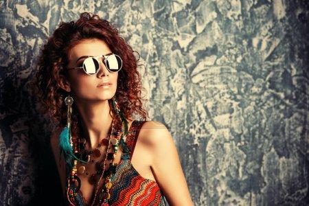 Photo pour Portrait de gros plan d'une belle femme brillante aux cheveux bouclés de foxy en perles, des boucles d'oreilles et des lunettes de soleil. Style ethnique dans les accessoires. - image libre de droit