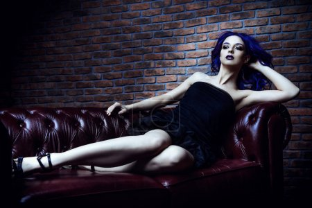 Photo for Attractive young woman in black dress with purple hair is sitting on a leather sofa. Beauty, youth fashion. Hair coloring. Cosmetics, make-up. - Royalty Free Image