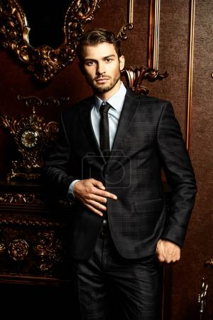 Photo for Imposing well dressed man in a luxurious apartments with classic interior. Luxury. Men's beauty, fashion. - Royalty Free Image