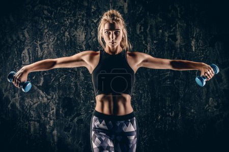 Photo for Beautiful athletic woman doing exercises with dumbbells. Fitness, bodybuilding. Health care. - Royalty Free Image