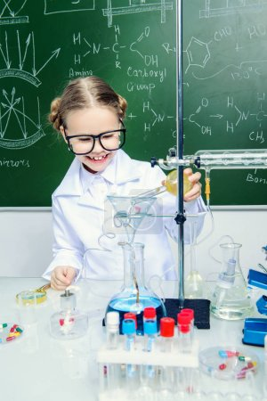 Photo for Serious little girl doing experiments in the laboratory. Explosion in the laboratory. Science and education. - Royalty Free Image