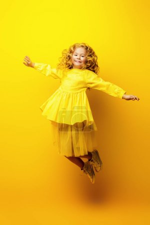 Photo for Children's fashion. Beautiful  little girl in yellow dress jumping at studio over yellow background. - Royalty Free Image