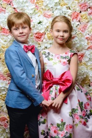 Photo pour Mode pour enfants. Beau garçon et fille en vêtements élégants posant sur un fond de roses . - image libre de droit