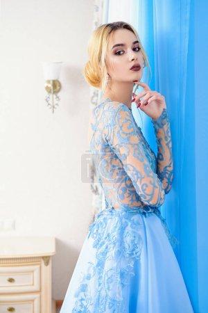 Photo pour Portrait d'une belle jeune femme en élégante robe bleue. Appartements de luxe . - image libre de droit