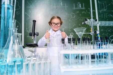Photo for Little girl scientist doing chemical experiments in the laboratory. Science and education. - Royalty Free Image