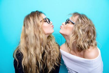 Photo for Two pretty cheerful girls in glasses are posing in studio over blue background. Beauty, fashion. Optics, eyewear. - Royalty Free Image