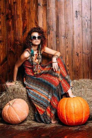 Photo pour Belle femme brillante aux cheveux bouclés de foxy est assis sur une botte de foin. Vêtements et accessoires dans le style boho. Style ethnique dans les vêtements. - image libre de droit