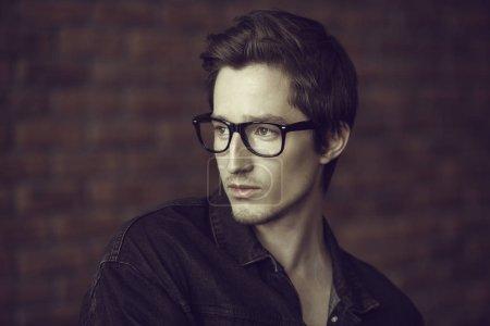 Photo pour Beauté masculine, mode. Beau jeune homme posant en lunettes et veste en denim noir près du mur de briques. Coiffure . - image libre de droit