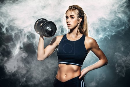 Photo for Muscular young woman with beautiful athletic body doing exercises with dumbbell. Fitness, bodybuilding. Health care. - Royalty Free Image